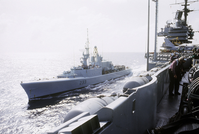 A port bow view of the Canadian Forces, St. Laurent Class, Frigate HMCS Fraser (F 233) sailing in position of the starboard side of the Forrestal Class, Aircraft Carrier USS SARATOGA (CV 60) in preparation for an underway replenishment