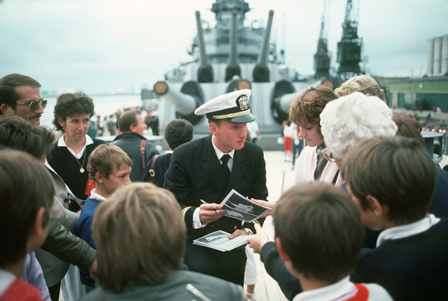 Lieutenant Junior Grade (LTJG) Rick Crigger signs welcome aboard brochures for visitors during a port visit by the battleship USS IOWA (BB 61)