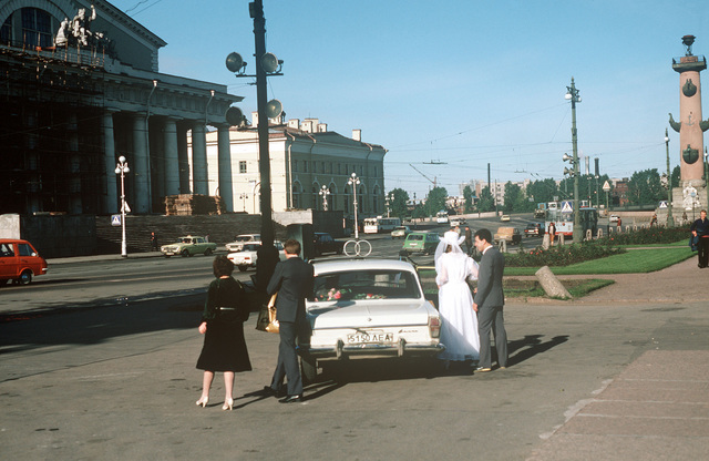 A young Soviet couple following their marriage. They are in front of the Central Naval Museum of the Red Navy. To the right is one of the historic lighthouse towers erected under the direction of Peter the Great in 1705