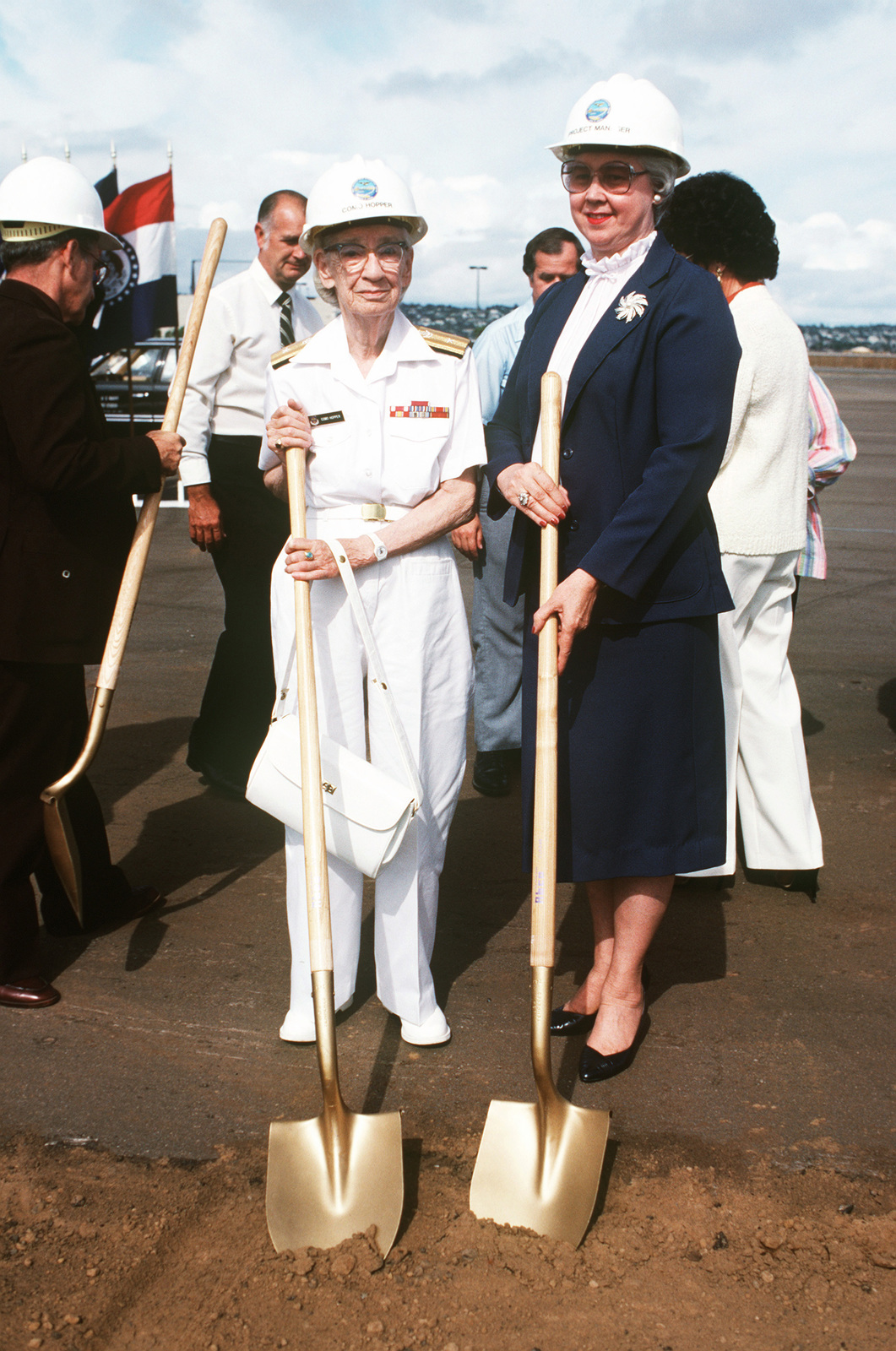 Commodore Grace M. Hopper, special assistant to the commander, Naval Data Automation Command, and Eva M. Sebastian, project manager, Navy Regional Data Automation Center, pose with ceremonial shovels at Rear Admiral John W. Nyquist, director, Surface Combat the groundbreaking ceremony for the Grace M. Hopper Navy Regional Data Automation Center, San Diego