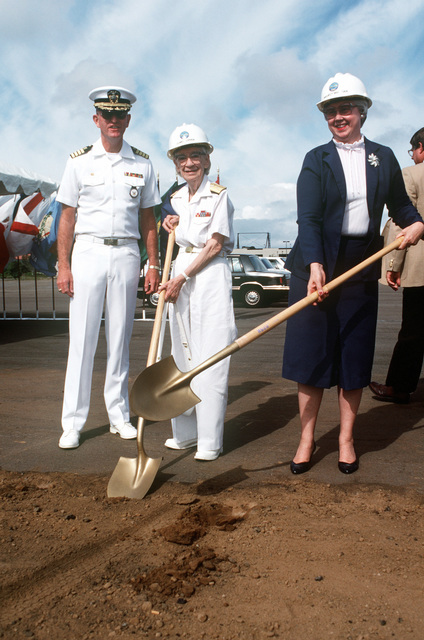 Commodore Grace M. Hopper, special assistant to the commander, Naval Data Automation Command, and Eva M. Sebastian, project manager, Navy Regional Data Automation Center, pose with ceremonial shovels at the groundbreaking ceremony of the Grace M. Hopper Navy Regional Data Automation Center, San Diego. Captain C. T. Smith, commanding officer, Navy Regional Data Automation Center, San Diego, is in the background