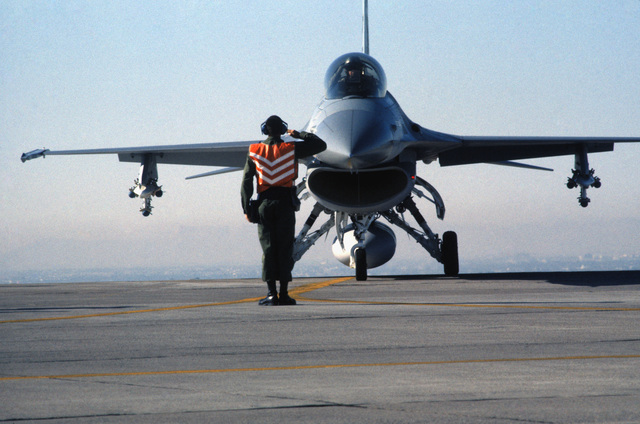 A ground crewman salutes the pilot of a 50th Tactical Fighter Wing F-16 Fighting Falcon aircraft prior to launch during Exercise GUNSMOKE '85