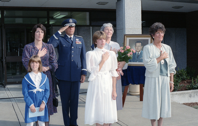 General (GEN) Robert D. Russ, commander, Tactical Air Command, and Mrs. Betty Worley, holding the bouquet, and other family members of the late Major General (MGEN) Robert F. Worley, honor the flag during a ceremony dedicating Worley Hall. A portrait of MGEN Worley, who was killed in action in Vietnam on July 23, 1968, is in the background