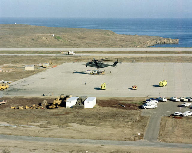 A Helicopter Combat Support Squadron 1 (HC-1), Fleet Angels, CH-53E Super Stallion helicopter prepares to release the forward section of an A-3D Skywarrior Aircraft on a stand on the ramp