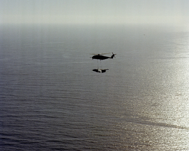 A Helicopter Combat Support Squadron 1 (HC-1), Fleet Angels, CH-53E Super Stallion helicopter carries the forward section of an A-3D Skywarrior Aircraft over the Pacific Ocean off the coast of San Clemente