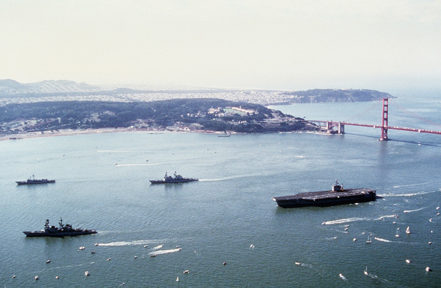 Aerial port view of the destroyer USS PAUL F. FOSTER (DD 964) followed by the guided missile destroyer USS CALLAGHAN (DDG 994) and the nuclear powered aircraft carrier USS CARL VINSON (CVN 70) after passing the Golden Gate bridge. A guided missile frigate is seen at left (background)