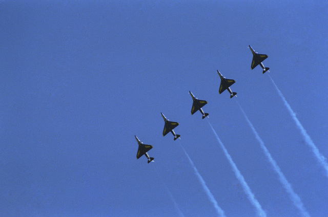 Five A-4F Skyhawk aircraft from the Blue Angels Flight Demonstration Squadron fly in formation over the bay during Fleet Week activities