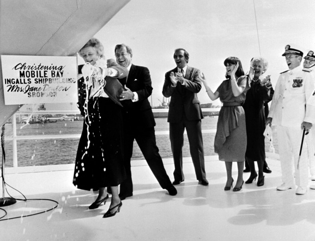Mrs. J. Denton, sponsor, breaks champagne across the bow of the guided missile cruiser MOBILE BAY (CG-53). Looking on are (L-R): Sen. J. Denton Jr., R-Als., Mr. J. St. Pe', president of Ingalls Shipbuilding; M. Denton, maid of honor; Mrs. M. McPhillips, matron of honor; Vice Adm. J. Metcalf III, deputy chief of Naval Operations, Surface Warfare; Rear Adm. W. Meyer, deputy commander, Combat Systems, Naval Sea Systems Command; and Commodore J. Shaw, program manager, Aegis Shipbuilding, Naval Sea Systems Command