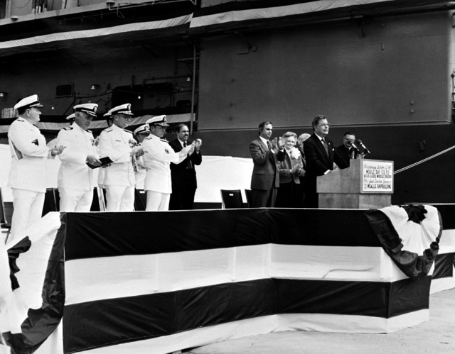 Sen J. Denton Jr., R-Ala., speaks at the christening of the Aegis guided missile cruiser MOBILE BAY (CG-53). Behind him are (L-R): Rear Adm. W. Meyer, deputy commander, Combat Systems, Naval Sea Systems Command; CAPT. G. Dowell III, supervisor of shipbuilding, conversion, and repair; Commodore J. Shaw, program manager, Aegis Shipbuilding, Naval Sea Systems Command; Vice Adm. J. Metcalf III, deputy chief of Naval Operations, Surface Warfare; Mr. Knecht,; Mr. J. St. Pe`; Jane Denton, sponsor; M. McPhillips, matron of honor; and Archbishop O. Lipscomb