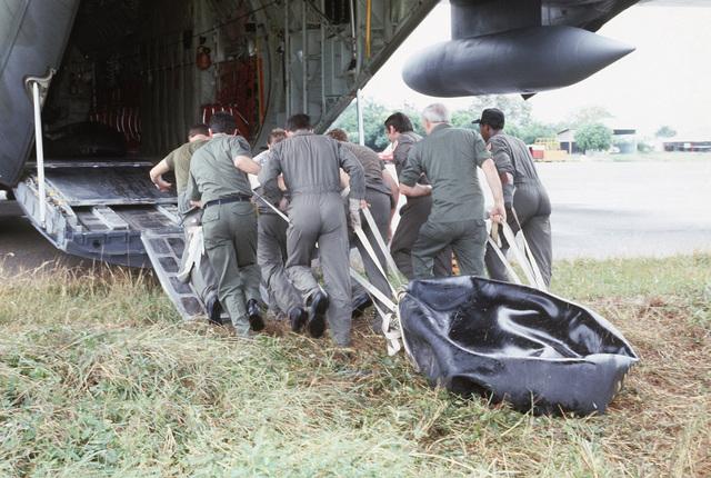US Air Force personnel drag an empty fuel bladder into the back of a C-130E Hercules aircraft during relief efforts for the victims of the Nevado del Ruiz volcano eruption