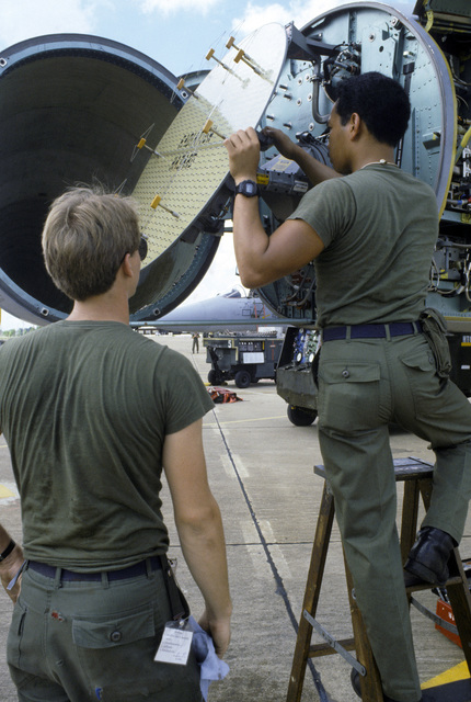 Senior AIRMAN (SRA) Segovia and AIRMAN First Class (A1C) James C. Samples III of the 18th Aircraft Generation Squadron replace the radar dish on a 67th Tactical Fighter Squadron F-15 Eagle aircraft during COMMANDO WEST IX, a joint US and Thailand training exercise