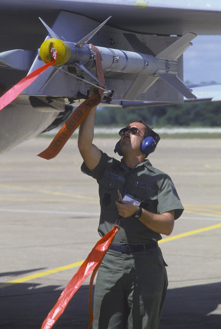 Technical Sergeant (TSGT) Albert E. Rivard of the 18th Equipment Maintenance Squadron removes the pins from an AIM-9 Sidewinder missile mounted on a 67th Tactical Fighter Squadron F-15 Eagle aircraft during COMMANDO WEST IX, a joint US and Thailand training exercise