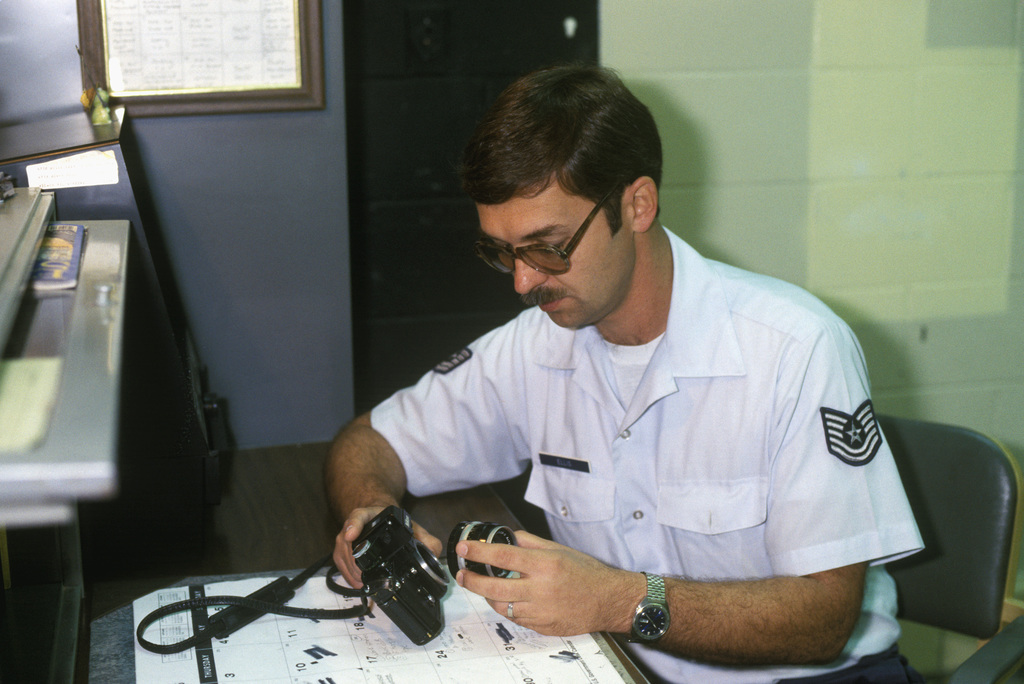 Technical Sergeant (TSGT) Charles Ellis, non-commissioned officer in charge of the base photo lab, makes a routine inspection on a 35 mm camera