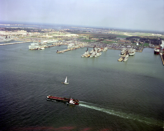 An elevated view of various ships moored at the destroyer and submarine piers. The submarine tenders USS L.Y. SPEAR (AS-36) and USS EMORY S. LAND (AS-39) are at the far left