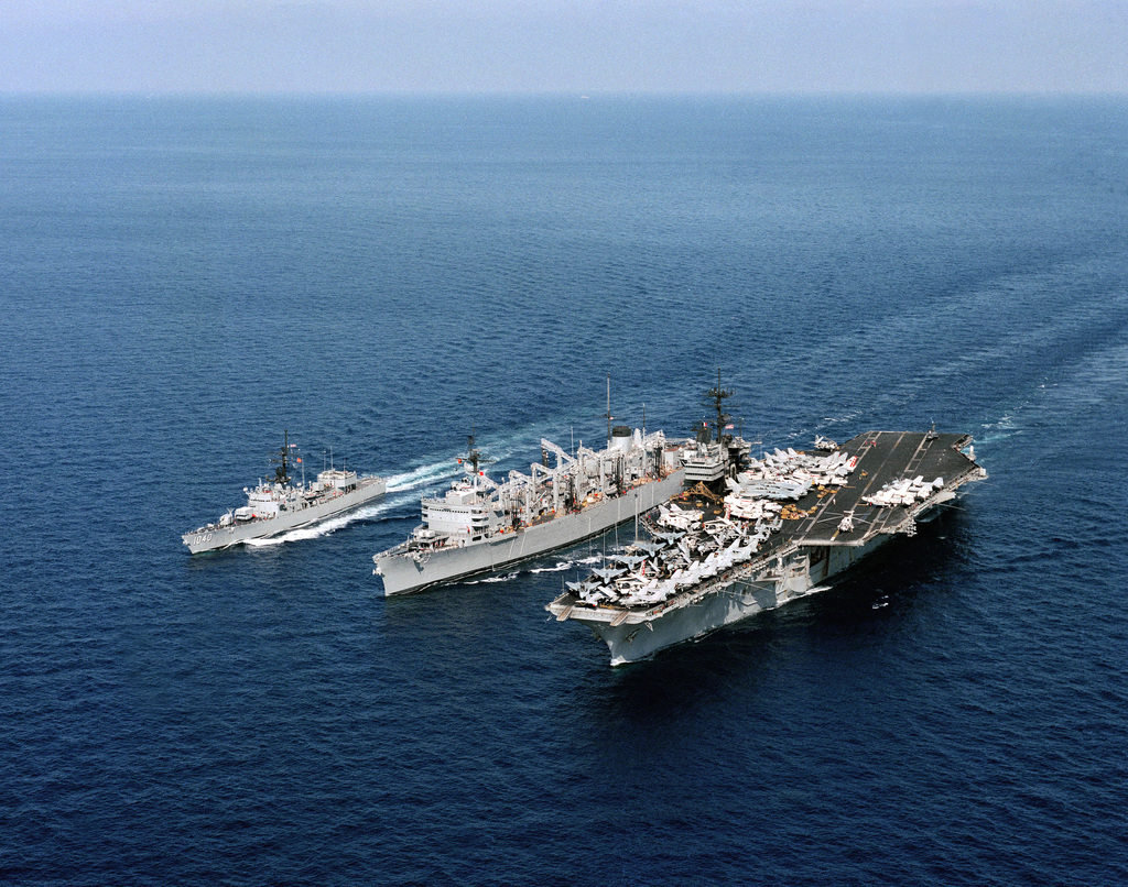 An elevated port bow view of the aircraft carrier USS SARATOGA (CV 60), the fast combat support ship USS SEATTLE (AOE 3) and the frigate USS GARCIA (FF 1040) participating in an underway replenishment