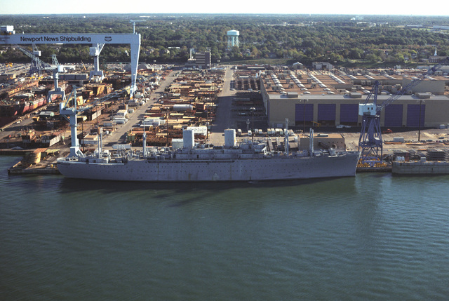A starboard beam view of the barracks ship USNS GENERAL WILLIAM O. DARBY (IX 510) moored at the Newport News Shipbuilding shipyard. To the left is the nuclear-powered aircraft carrier USS ABRAHAM LINCOLN (CVN 72) under construction