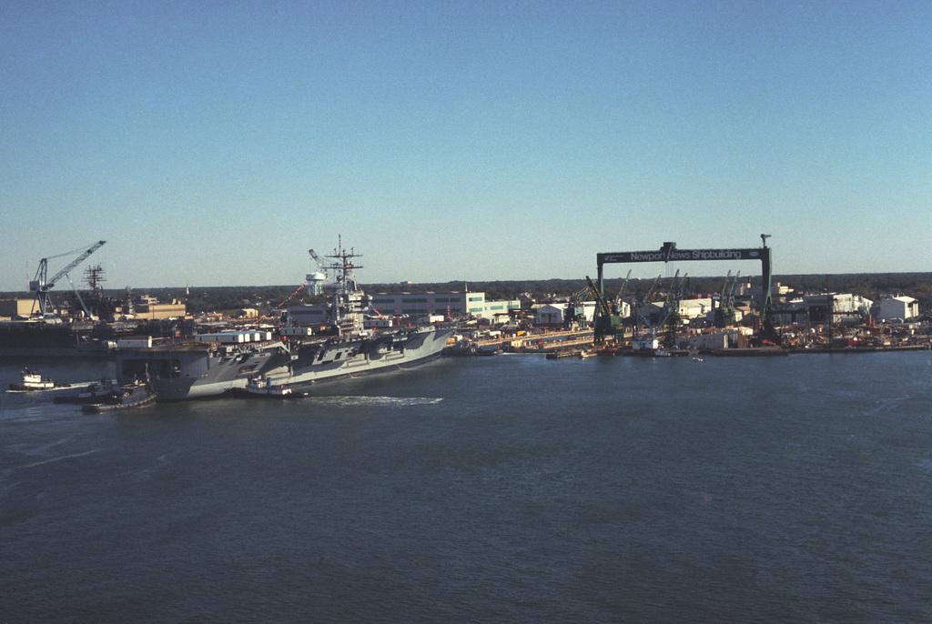 Tugs assist the nuclear-powered aircraft carrier USS DWIGHT D. EISENHOWER (CVN 69) into a dry dock at the Newport News Shipbuilding shipyard