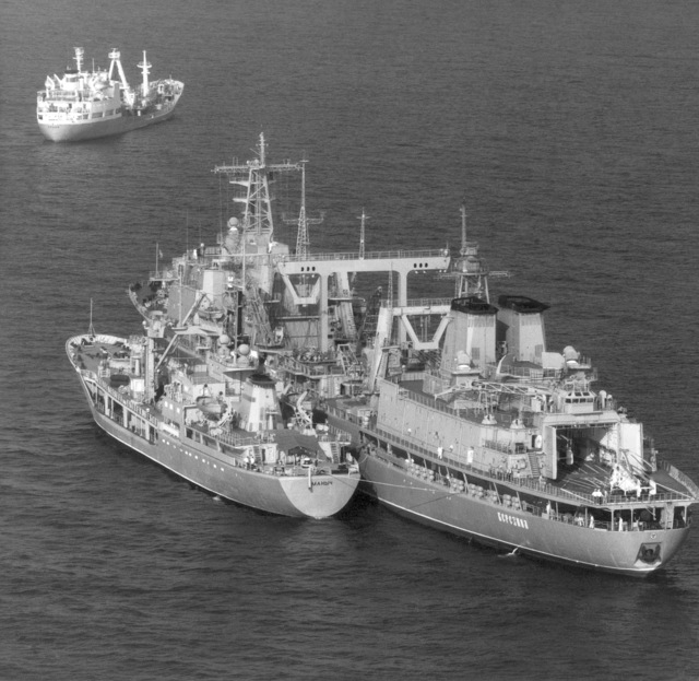 Aerial port quarter view of the Soviet fresh water tanker MANYCH, (left) and the large replenishment ship BEREZINA, at an open-ocean anchorage
