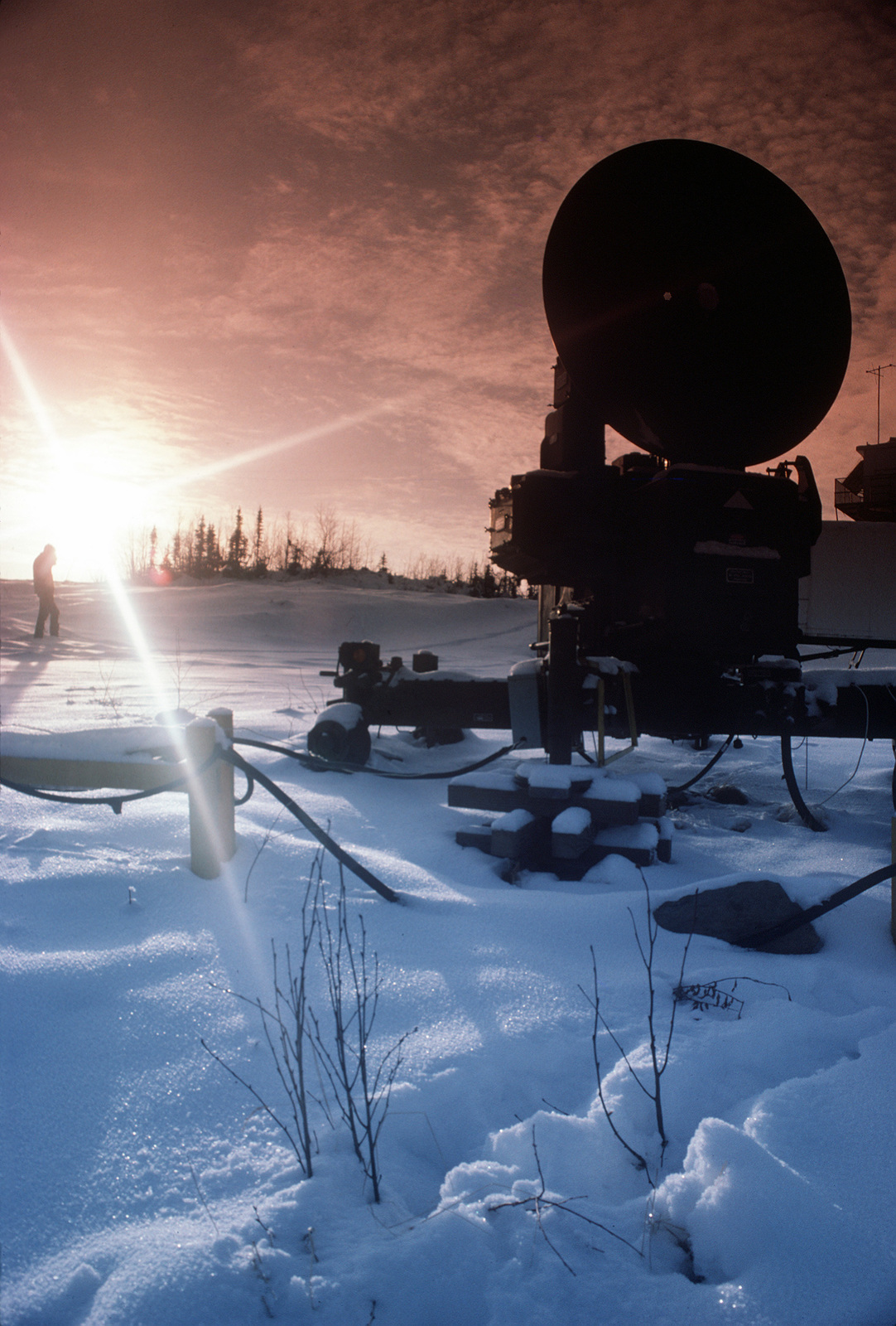 A microwave relay station system used for transmitting video from the range to Eielson Air Force Base is silhouetted by the sun. The relay station is maintained by the 5055th Range Squadron from Eielson and is used to help duplicate electronic threats that Air Force pilots would expect to face in actual battle