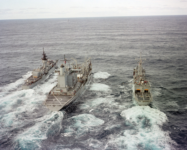 A stern view of the fleet oiler USS MERRIMACK (AO 179), center, refueling the guided missile frigate USS HALYBURTON (FFG 40), right, and the frigate USS AYLWIN (FF 1081)