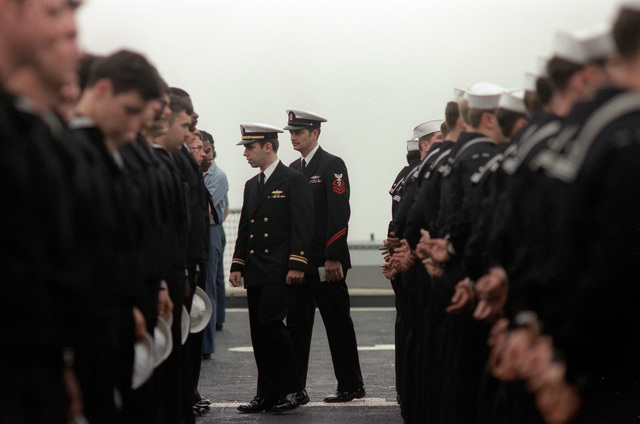 Lieutenant Junior Grade John Donovan and CHIEF Machinist's Mate Chris Archut inspect the crew of Division M aboard the battleship USS IOWA (BB-61). The IOWA is returning from a three month deployment to the Baltic Sean and North Atlantic