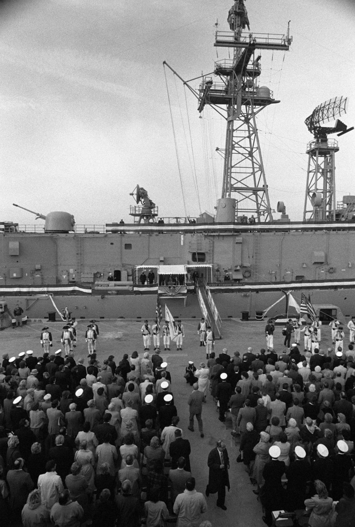 An overall view of the Newport Artillery Unit (left), the Colonial Navy of Massachusetts (center to right), and crowd during the commissioning ceremony for the guided missile frigate USS SIMPSON (FFG 56). The ship is seen in the background