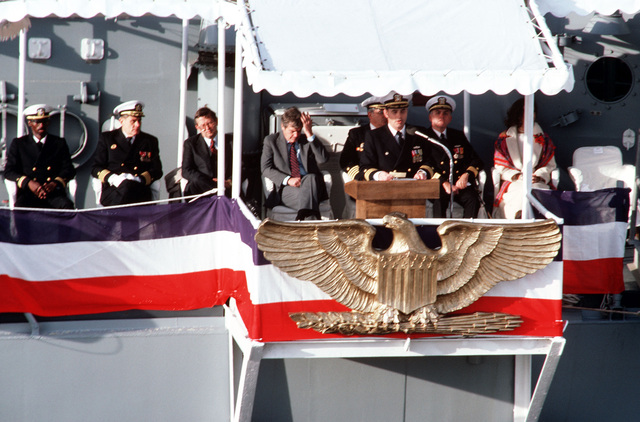 Commander H. Wyman Howard Jr. accepts command of the guided missile frigate USS SIMPSON (FFG 56) during the ship's commissioning ceremony. Members of the commissioning party are seated on the speaking platform. (R-L) Rep. Claudine Schneider, R-RI; Commodore David F. Chandler, deputy commander, Naval Surface Force, US Atlantic Fleet; and Mr. William E. Haggett, president and chief executive officer of Bath Iron Works Corp
