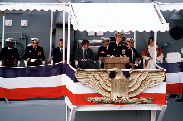 Commander H. Wyman Howard Jr. speaks during the ship's commissioning ceremony for the guided missile frigate USS SIMPSON (FFG 56). Seated behind him are (R-L) Rep. Claudine Schneider, R-RI; Commodore David F. Chandler, deputy commander, Naval Surface Force, US Atlantic Fleet; and Mr. William E. Haggett (fourth left), president and chief executive officer of Bath Iron Works Corp; and Captain William A. Rehder (sixth left), supervisor of Shipbuilding, Conversion, and Repair