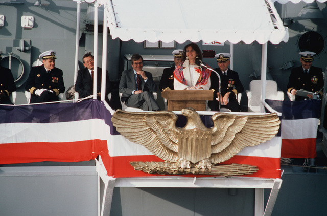 Representative Claudine Schneider, R-RI, speaks during the commissioning of the guided missile frigate USS SIMPSON (FFG 56). Seated behind he (L-R) are: Lieutenant J.P.W. Poole, Chaplain Corps; Captain W.A. Rehder, supervisor, Shipbuilding, Conversion and Repair; W.E. Haggett (fourth left), president and chief executive officer, Bath Iron Works; Captain Paul P. Aquilino, commander, Naval Surface Force Four, Commodore D.F. Chandler, deputy commander, Naval Surface Force, Atlantic Fleet, and Commander H.W. Howard Jr., commanding officer of the SIMPSON