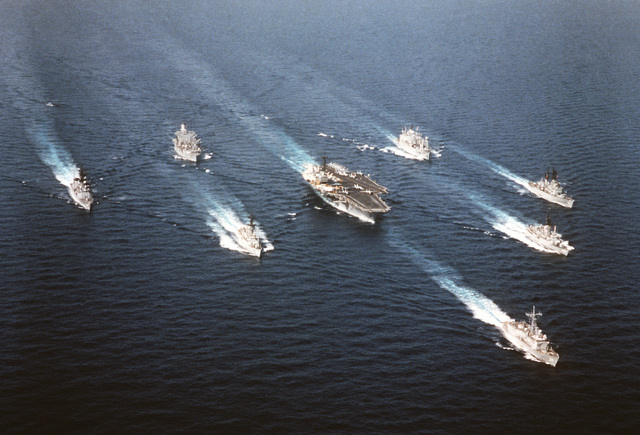 An aerial starboard bow view of the aircraft carrier USS SARATOGA (CV-60) and its battle group underway. Clockwise from bottom: USS JACK WILLIAMS (FFG-24), USS JESSE L. BROWN (FF-1089), USS SCOTT (DDG-995), USS MONONGAHELA (AO-178), USS MOUNT BAKER (AE-34), USS BIDDLE (CG-34), USS CAPODANNO (FF-1093), and USS SARATOGA (CV-60)