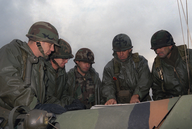 STAFF members of the 1ST Battalion, 27th Infantry, 25th Infantry Division, review training plans for the upcoming bilateral training Exercise ORIENT SHIELD. The exercise will involve US and Japanese soldiers. Standing from left to right are Command Sergeant Major (CSM) James C. Williams, Captain (CPT) Chuck Williams, Major (MAJ) Cliff Rippeger, Lieutenant Colonel (LTC) David A. Crittenden, commander of the 1st Battalion, and CPT Joe Pineau