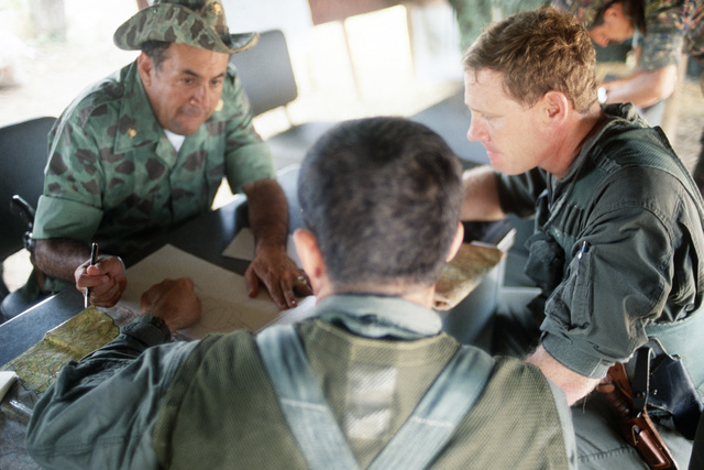 A Colombian army officer discusses rescue efforts with members of the 214th Medical Detachment during an international disaster relief effort following the eruption of a volcano
