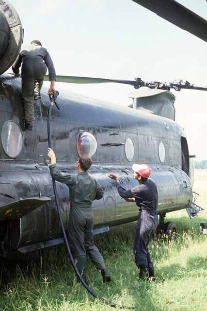 Maintenance crewmen of the 320th General Aviation Support Company wash a CH-47 Chinook helicopter while participating in an international disaster relief effort following the eruption of a volcano