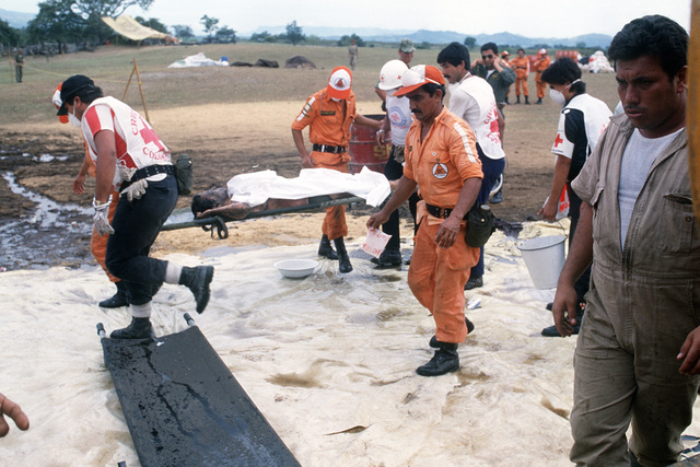 The victims of a mudslide that followed a volcanic eruption is carried into the traige area for treatment and transportation to a hospital