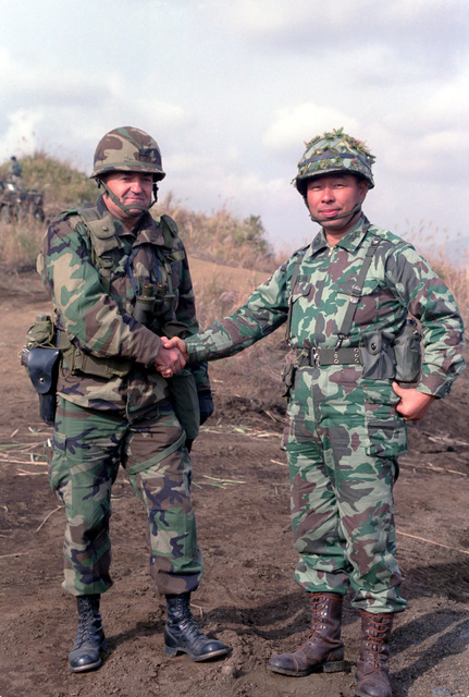 Colonel (COL) Thomas B. Vaughn, commander, 1ST Brigade, Task Force Lancer, 25th Infantry Division, left, shakes hands with COL Masatare Ando, commander, 1ST Regimental Combat Team, 1ST Infantry Division, Japanese Self Defense Force, at the conclusion of the joint US/Japanese Exercise ORIENT SHIELD '85
