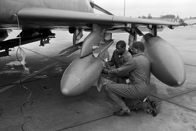Staff Sergeant (SSGT) Dwayne Griffin and Sergeant (SGT) Tommy Smith from the 70th Aircraft Maintenance Unit secure an F-4E Phantom II aircraft travel pod for flight