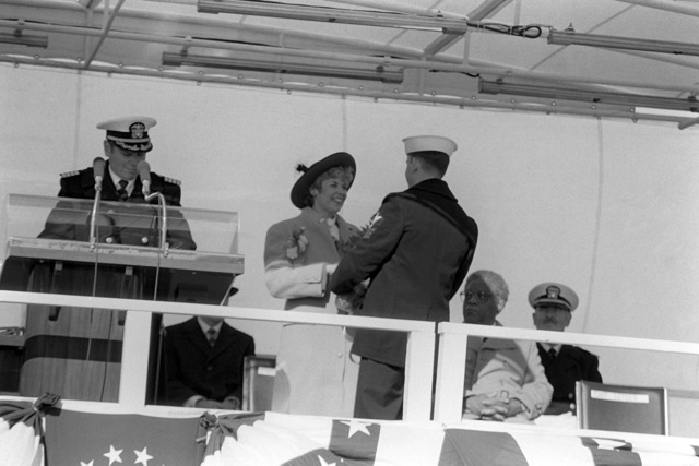 PETTY Officer Thomas Schumaker, USS PITTSBURGH (SSN 720) sailor of the year, gives flowers to Mrs. Carol Sawyer, ships sponsor, during the commissioning ceremony for the nuclear-powered attack submarine. To the left of Mrs. Sawyer is Captain Raymond H. Setser, commanding officer
