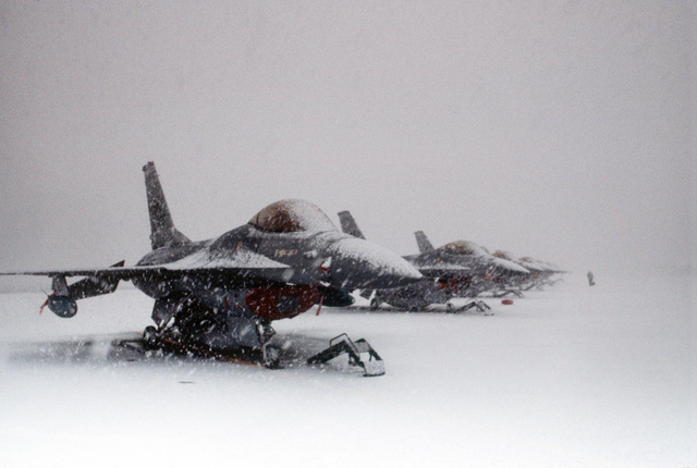 Snow falls on F-16A Fighting Falcon aircraft of the 13th Tactical Fighter Squadorn sitting on the flight line. The 13th is part of the 432nd Tactical Fighter Wing that was activated in 1984