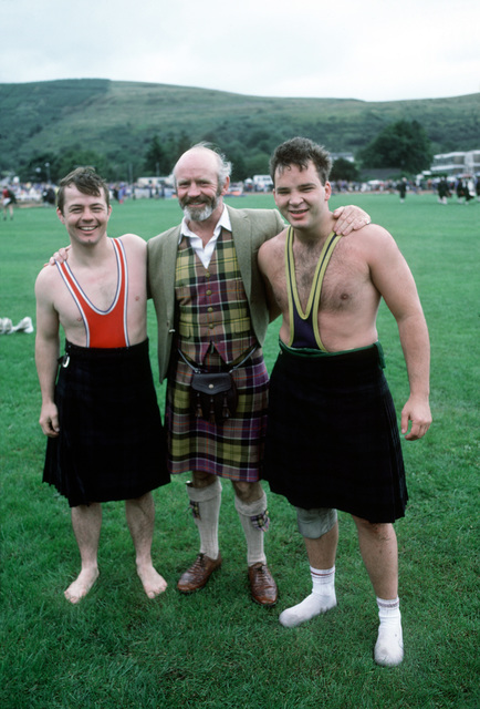 Two sailors assigned to Navy Fleet Ballistic Submarine Refit Site 1 at Holy Loch pose for a photograph with the former Scottish national wrestling coach, Wullis Baxter. They are wrestling during the Cowal Highland Gathering, a competition of traditional Scottish events