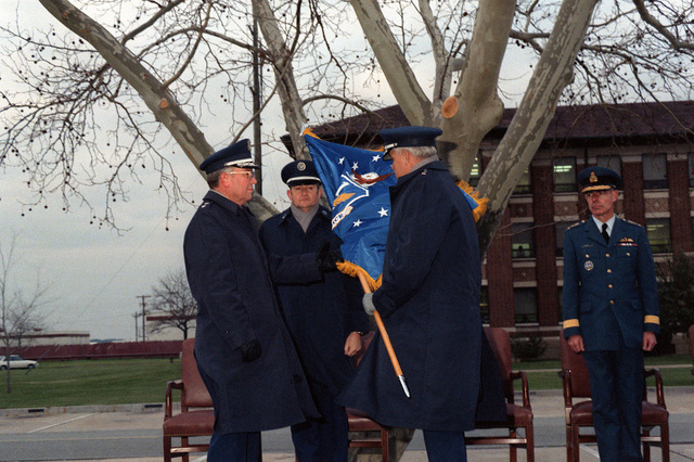 GEN Robert D. Russ, commander, Tactical Air Command (TAC), hands the 1ST Air Force (1ST AF) colors to MGEN Buford D. Lary, left, commander, Air Defense TAC (ADTAC), during the reactivation of the 1ST AF and the installation of Lary as its commander. Between them is CMSGT Douglas A. Hassler, senior enlisted advisor, ADTAC. At right is Royal Canadian Air Force LGEN Pablo McKenzie of the North American Aerospace Defense Command (NORAD). The 1ST AF will assume the mission of ADTAC, which is being dissolved