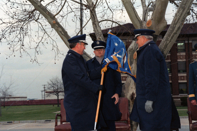 MGEN Buford D. Lary, left, commander, Air Defense Tactical Air Command (ADTAC), accepts the 1ST Air Force colors from GEN Robert D. Russ, right, commander, Tactical Air Command, at a ceremony marking the reactivation of the 1ST Air Force and the installation of Lary as its commander. CMSGT Douglas A. Hassler, senior enlisted advisor, ADTAC, stands between the two. The 1ST AF will assume the mission of ADTAC, which is being dissolved