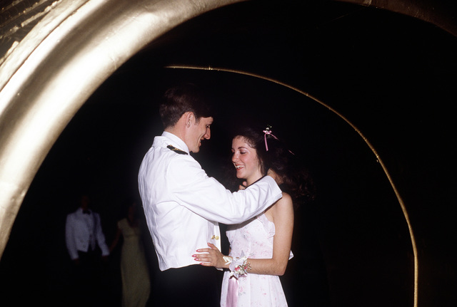 A senior midshipman and his date stand in the archway of the ring during the senior classman's ring dance. During the dance many seniors propose to their sweethearts here