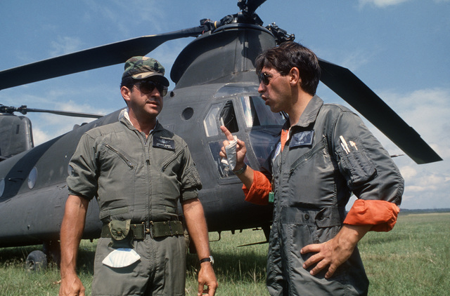 A member of the 210th Combat Aviation Battalion discusses helicopter maintenance with a member of the Colombian air force during relief efforts for victims of the Nevado del Ruiz volcano eruption. A CH-47 Chinook helicopter is in the background