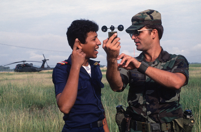 A member of the US Air Force 5th Weather Wing demonstrates a wind testing mechanism to a Colombian soldier during relief efforts for victims of the Nevado del Ruiz volcano eruption