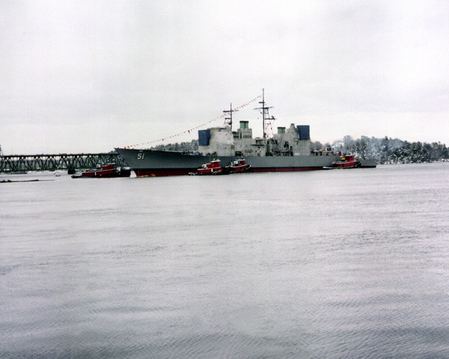 A port bow view of the guided missile cruiser THOMAS S. GATES (CG-51) on the Kennebec River after being launched. The ship is being assisted by four tugboats
