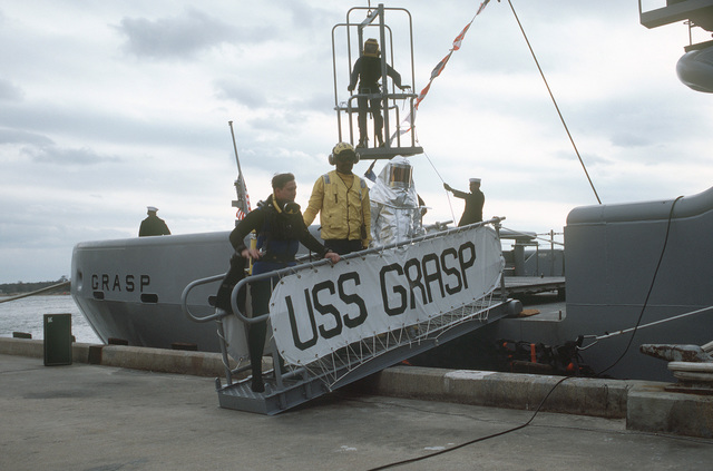A scuba diver, a flight deck crewman and a firefighter stand on the brow during the commissioning of the salvage ship USS GRASP (ARS 51). A diver is in a diving cage in the background