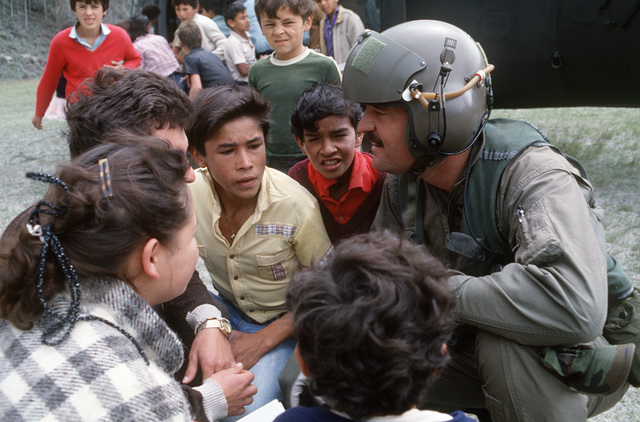 A UH-60 Blackhawk (Black Hawk) helicopter pilot from the 210th Combat Aviation Battalion asks local town representatives about supplies they need during relief efforts following the eruption of the Nevado del Ruiz volcano