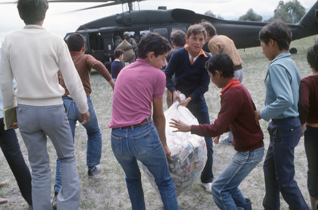 Colombian children help transport supplies from an Army UH-60 Blackhawk (Black Hawk) helicopter during relief efforts by the 210th Combat Aviation Battalion after the eruption of the Nevado del Ruiz volcano