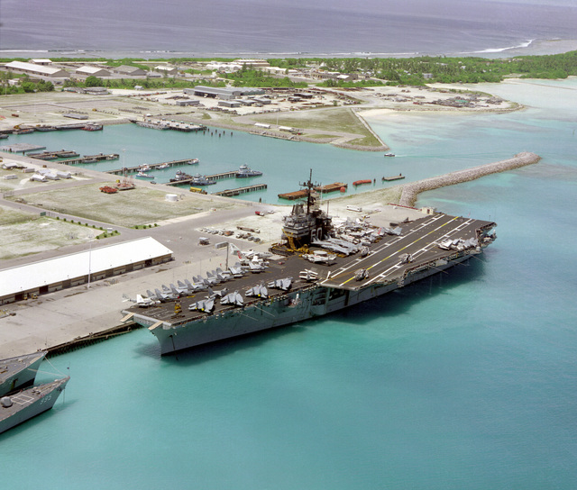 An aerial port bow view of the aircraft carrier USS SARATOGA (CV-60) tied up at pier. This is the first time an aircraft carrier has visited the island