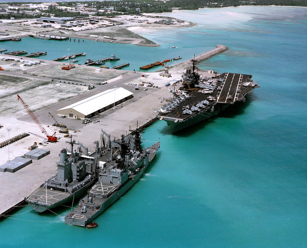 An aerial view of the aircraft carrier USS SARATOGA (CV 60), the guided missile destroyer USS SCOTT (DDG 995), and the fleet oiler USS MONONGAHELA (AO 178) tied up at pier. This is the first time an aircraft carrier has visited the island